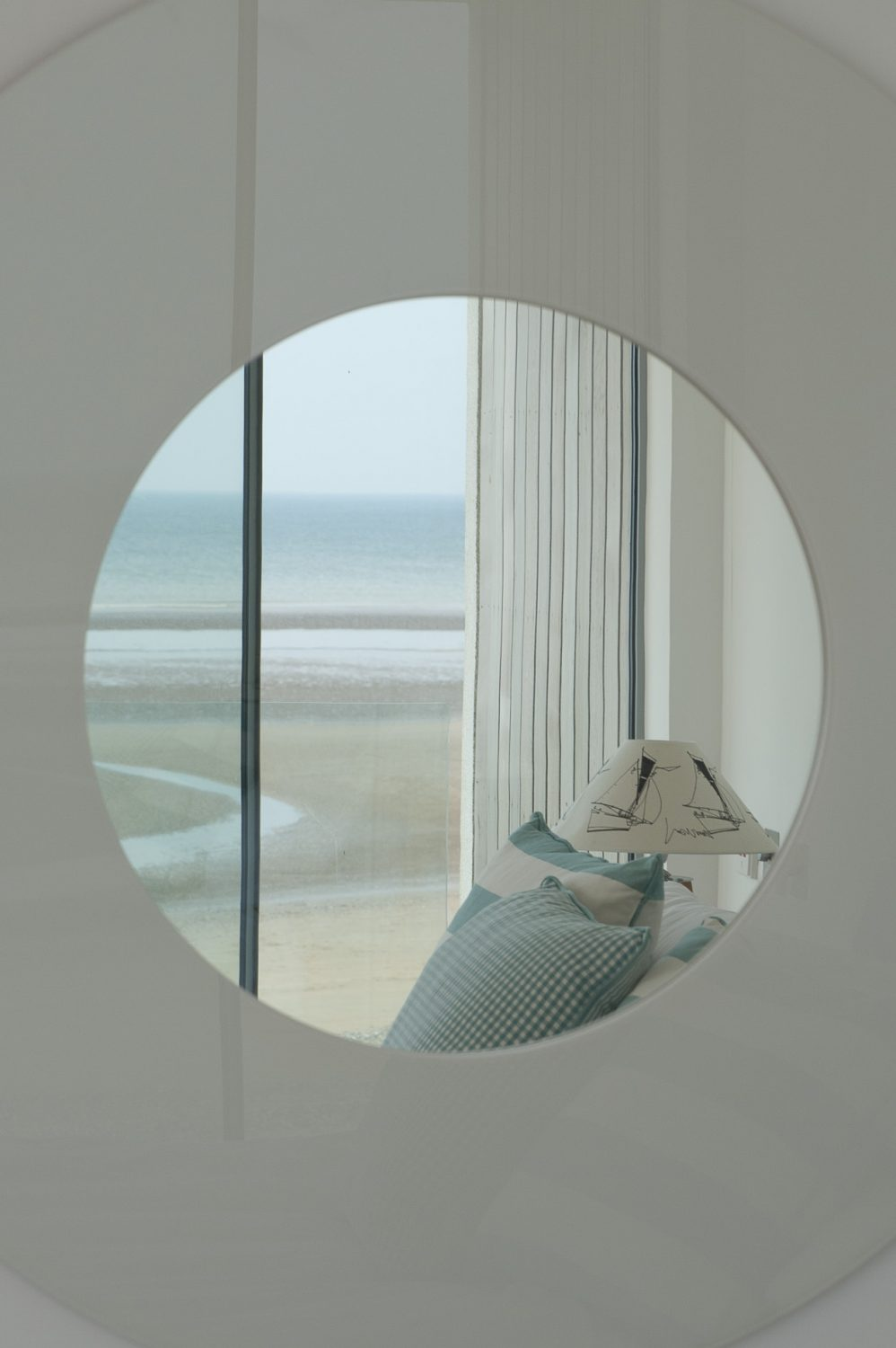 Next door, a large circular mirror on the wall faces the beach