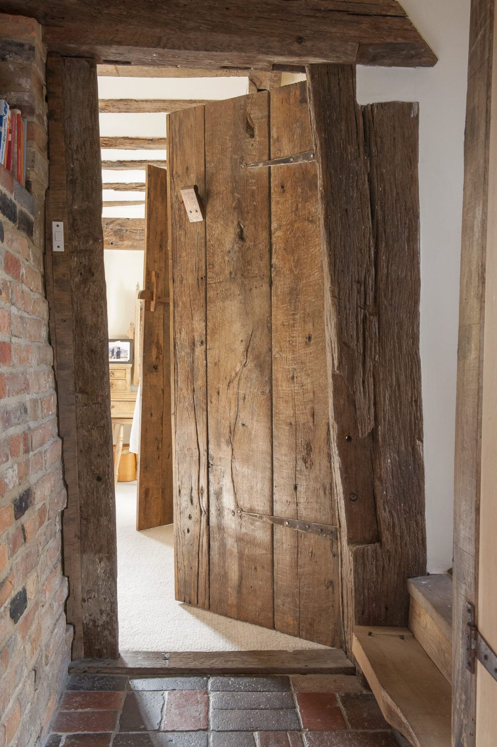Paul points out the impressive oak doors made from floorboards from the original cottages and which appear throughout the house