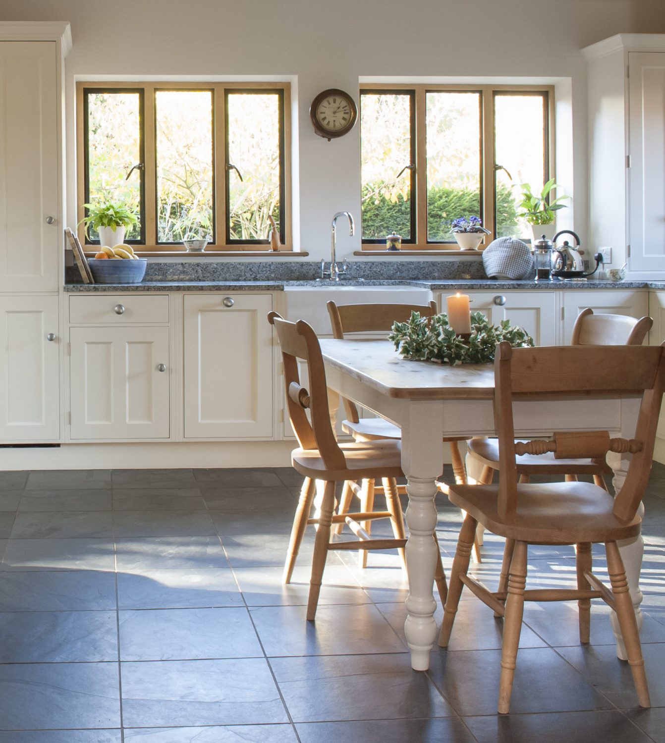 Light grey granite work surfaces and grey slate floor blend effortlessly with the ivory-coloured units and pewter handles