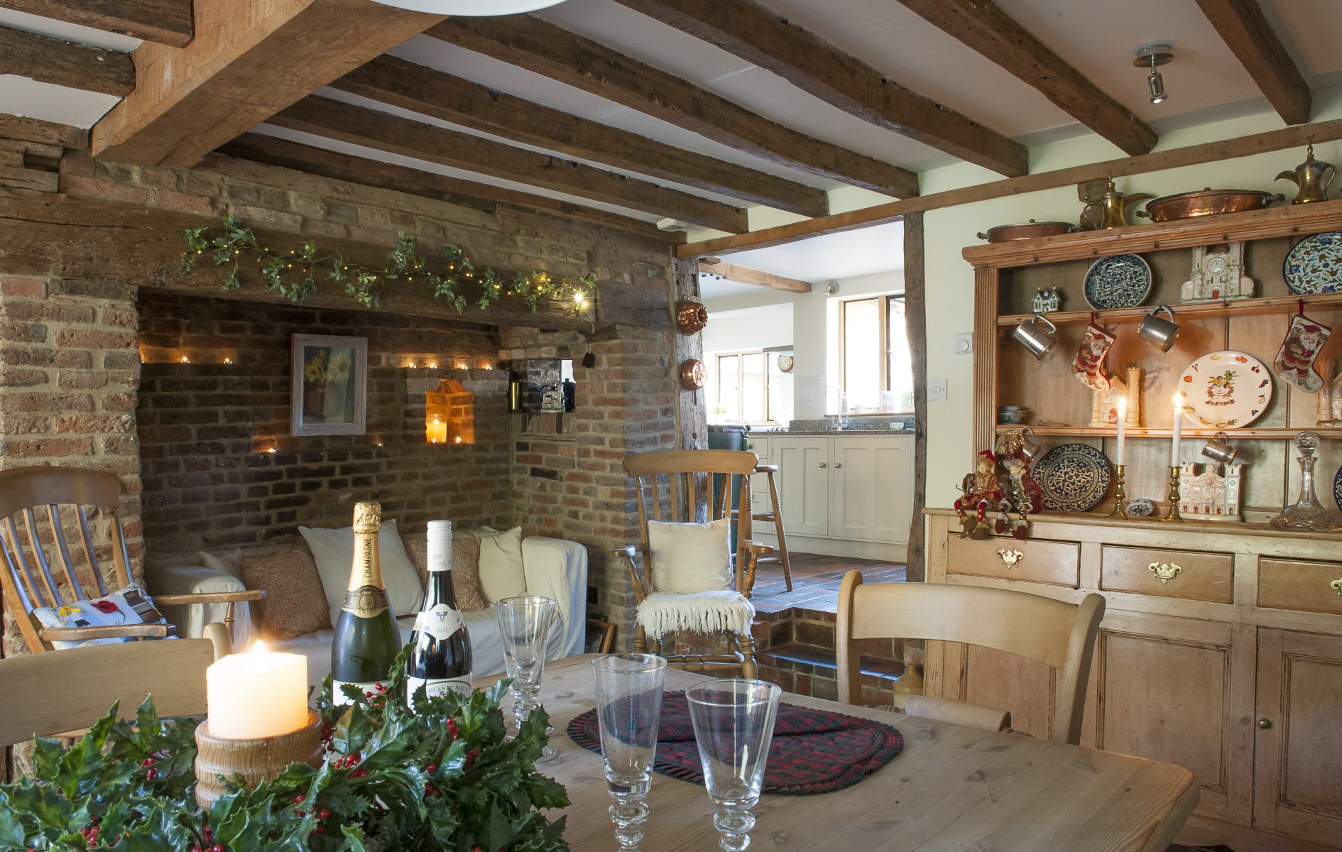 Focal point of the dining room is an impressive inglenook fireplace. Candles, hidden in the ledges and alcoves, add a relaxed amber glow to the room