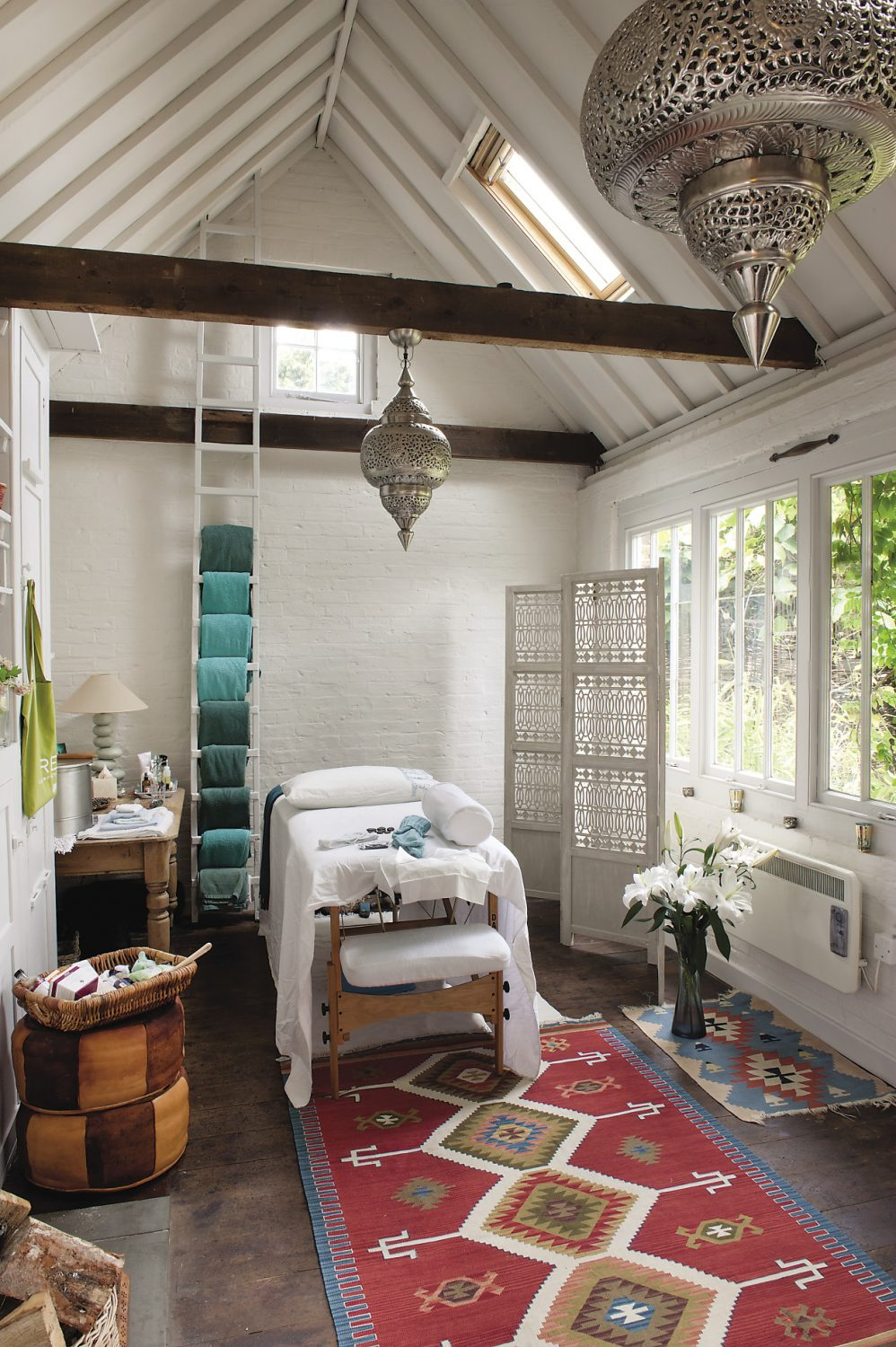 """Inside, Ann's Therapy Shed is painted a gentle white and from the beams crossing its high ceiling hang two silver coloured Moroccan metal lanterns. There is a colourful kilim on the floor. """"That's from Hoopers in Tunbridge Wells"""" says Ann. """"I have cotton kilims in here in the summer and woollen dhurries in the colder months. The wooden floor is used for yoga but the whole room is beautifully warm when we use the wood-burning stove."""