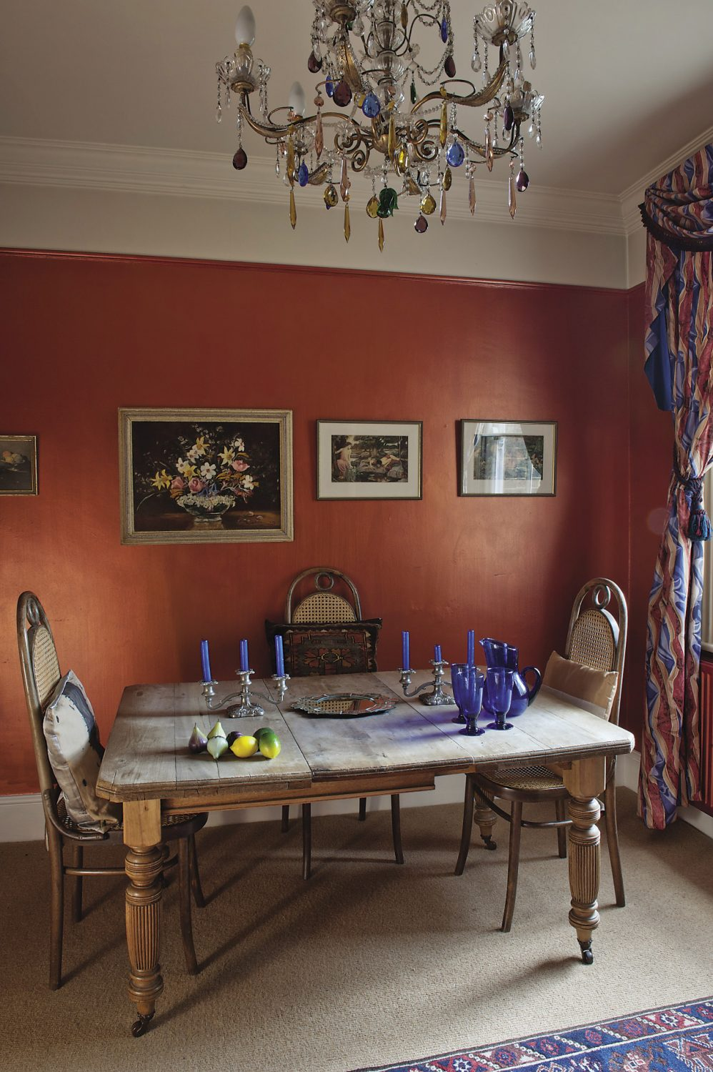 The dining room walls are painted a warm terracotta with a Jocasta Innes copper wash over the top, giving them a kind of iridescent sheen. A Murano glass chandelier is hung with coloured glass fruit-like droplets