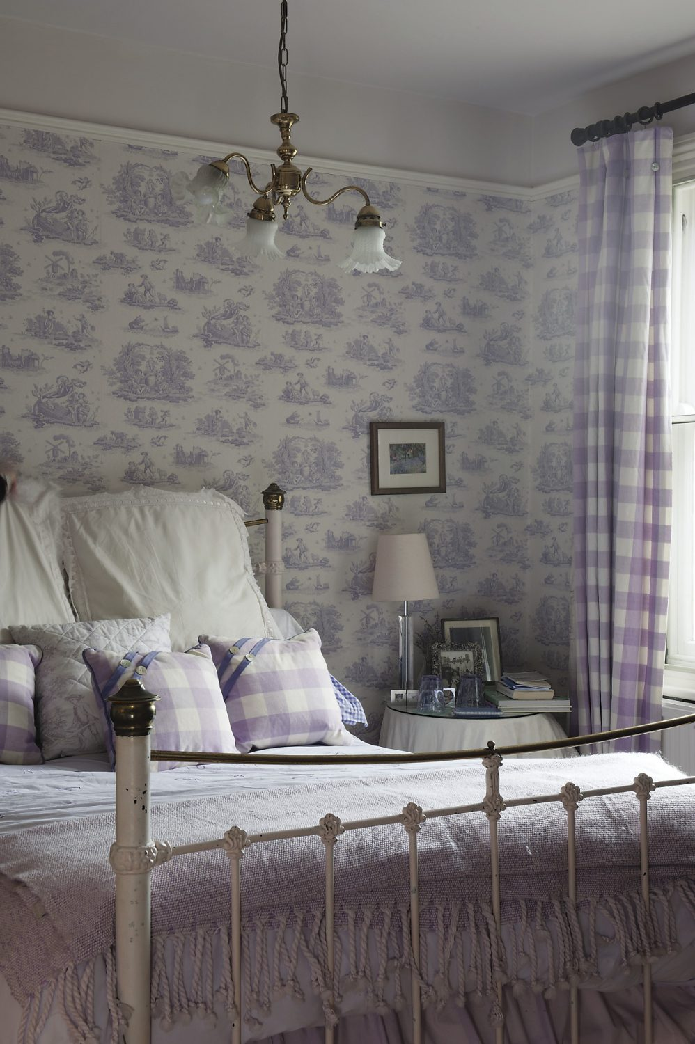 The guest room seems rather different in style to the rest of the house, but it is known as Ann's mother's room, so the lilac toile wallpaper and white embroidered bedlinen makes a fittingly relaxing environment