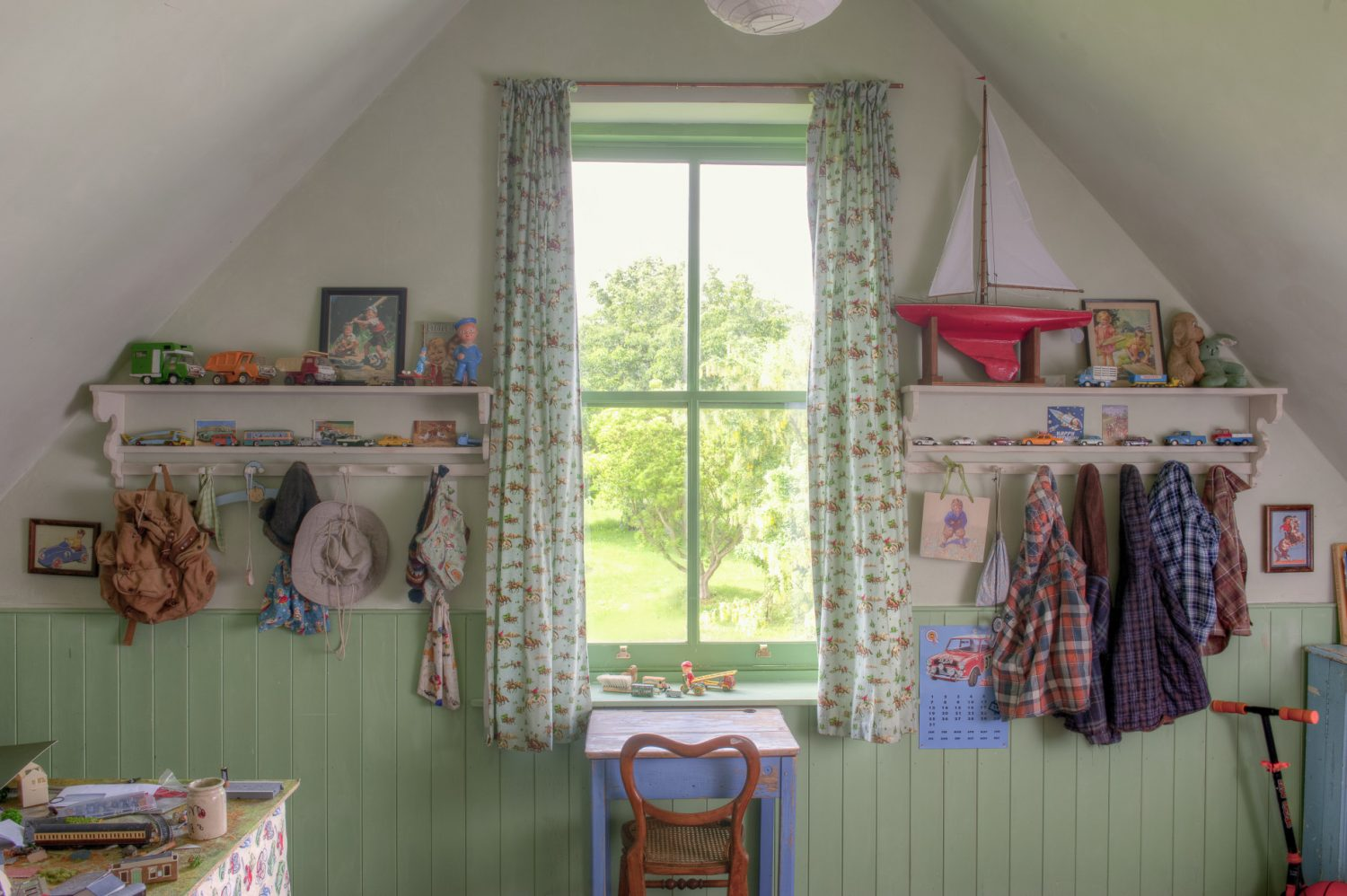 Son Cody's bedroom, at the centre of the house, occupies a prime position overlooking the garden and meadow beyond. Its apple green walls are lined with 1950s transport posters, Dinky Toys and vintage alphabet cards