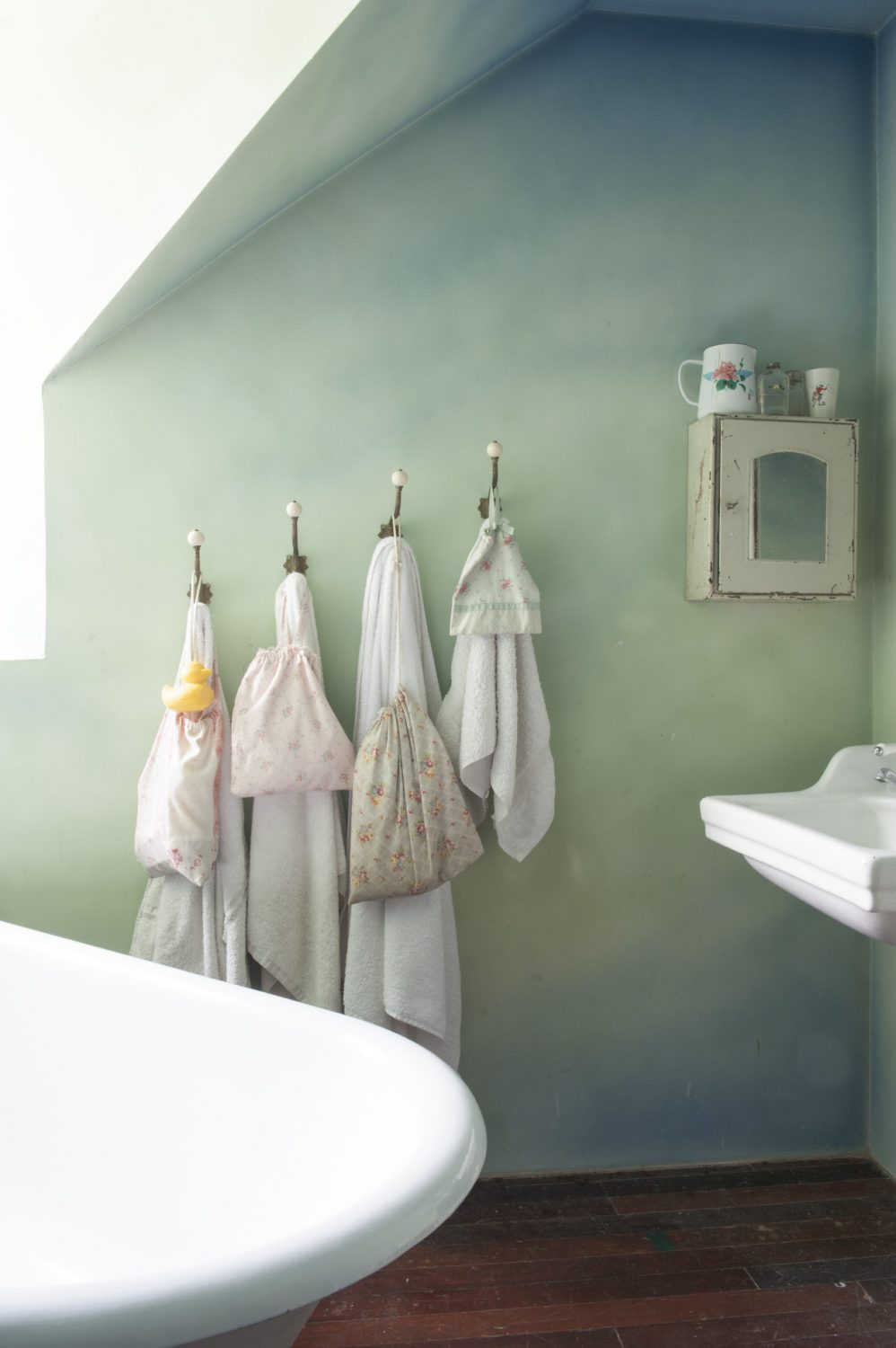 The bespoke children's decoration continues in their bathroom where the walls have been painted in layers of green-blue