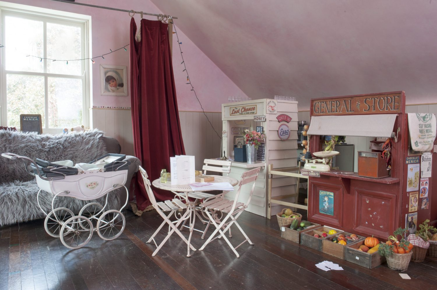The doorway is draped with theatrical swagged red velvet curtains. Inside, a painted wooden café kiosk and kitchen, a general store and a post office have been carefully crafted and painted by the couple for their three children to play with