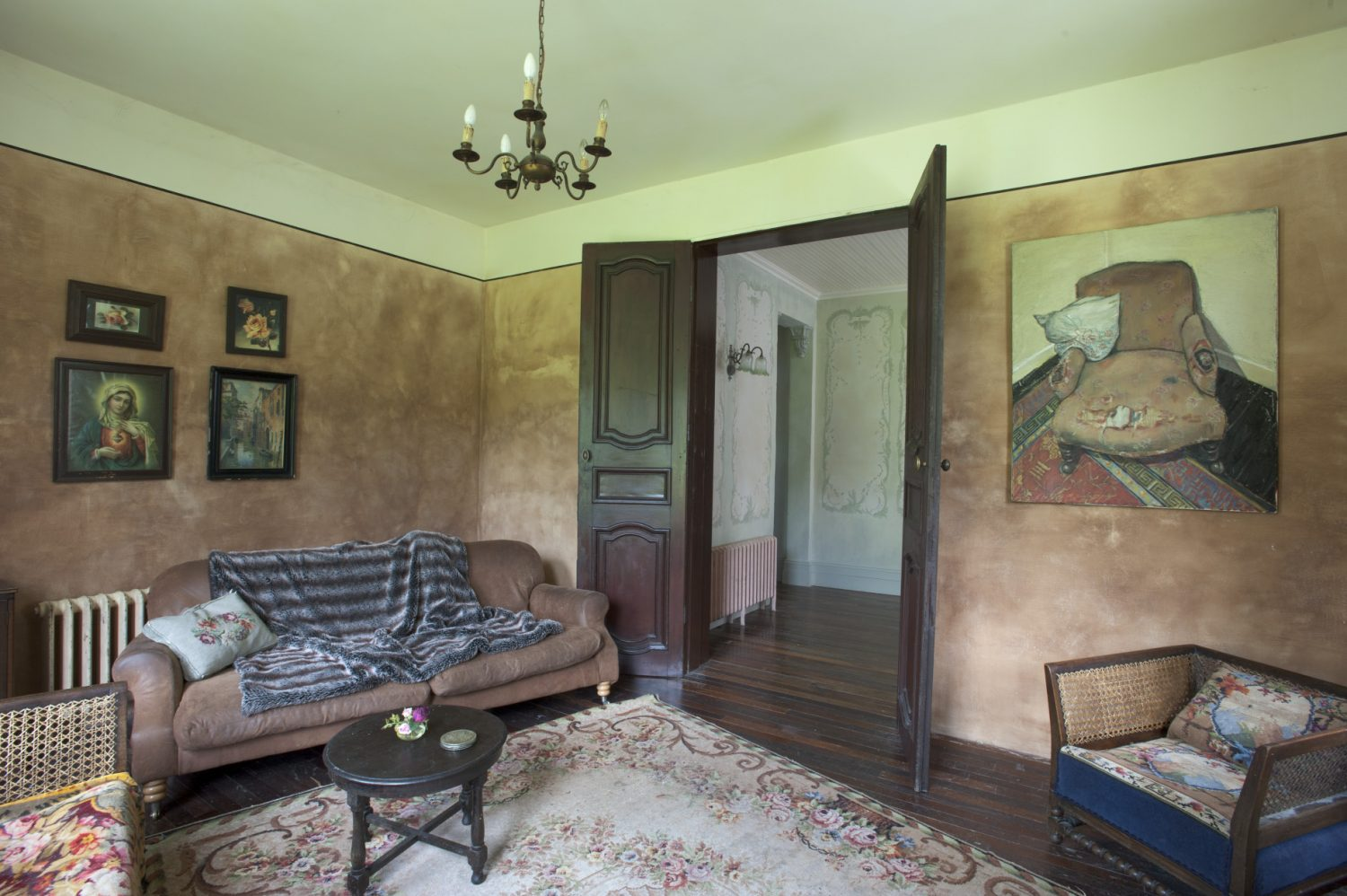 Leading off the rear hallway, the sitting room strikes a change of tone with its plaster pink walls and tobacco brown leather and cane sofas
