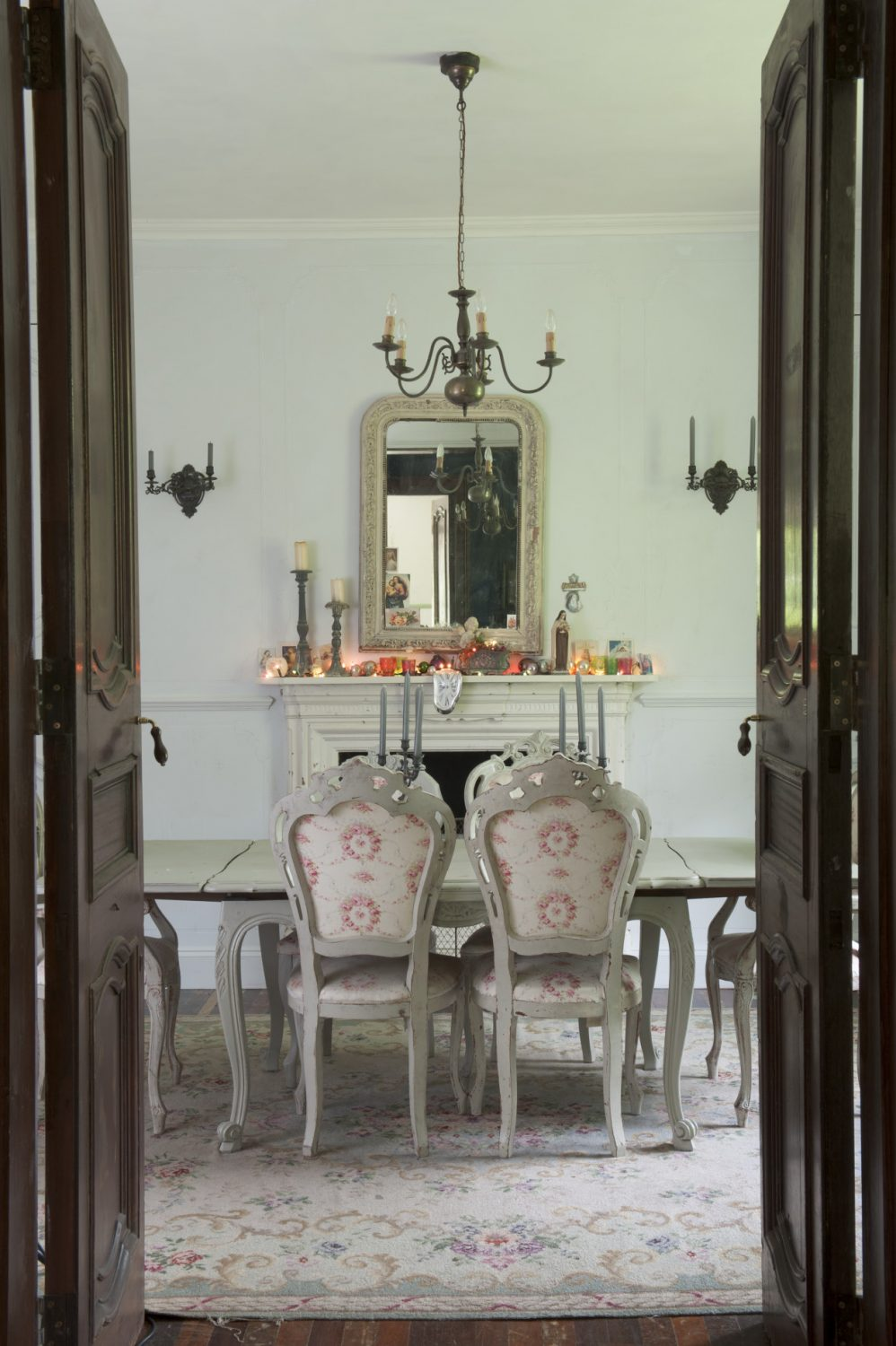 In the dining room, a false chimneybreast has been created and a reclaimed and painted fireplace and mantelpiece glows with soft blossom pink fairy lights and baubles