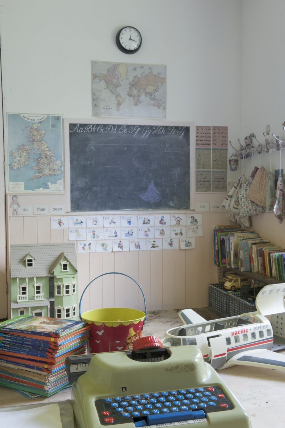 The downstairs playroom features classic schoolroom chalkboards and world maps