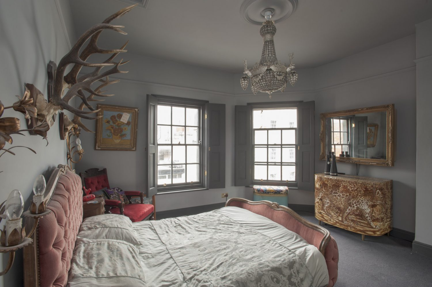 In the master bedroom the period French bed, framed by sets of antlers is upstaged by the superb, bow-fronted 1970s Fornasetti chest of drawers