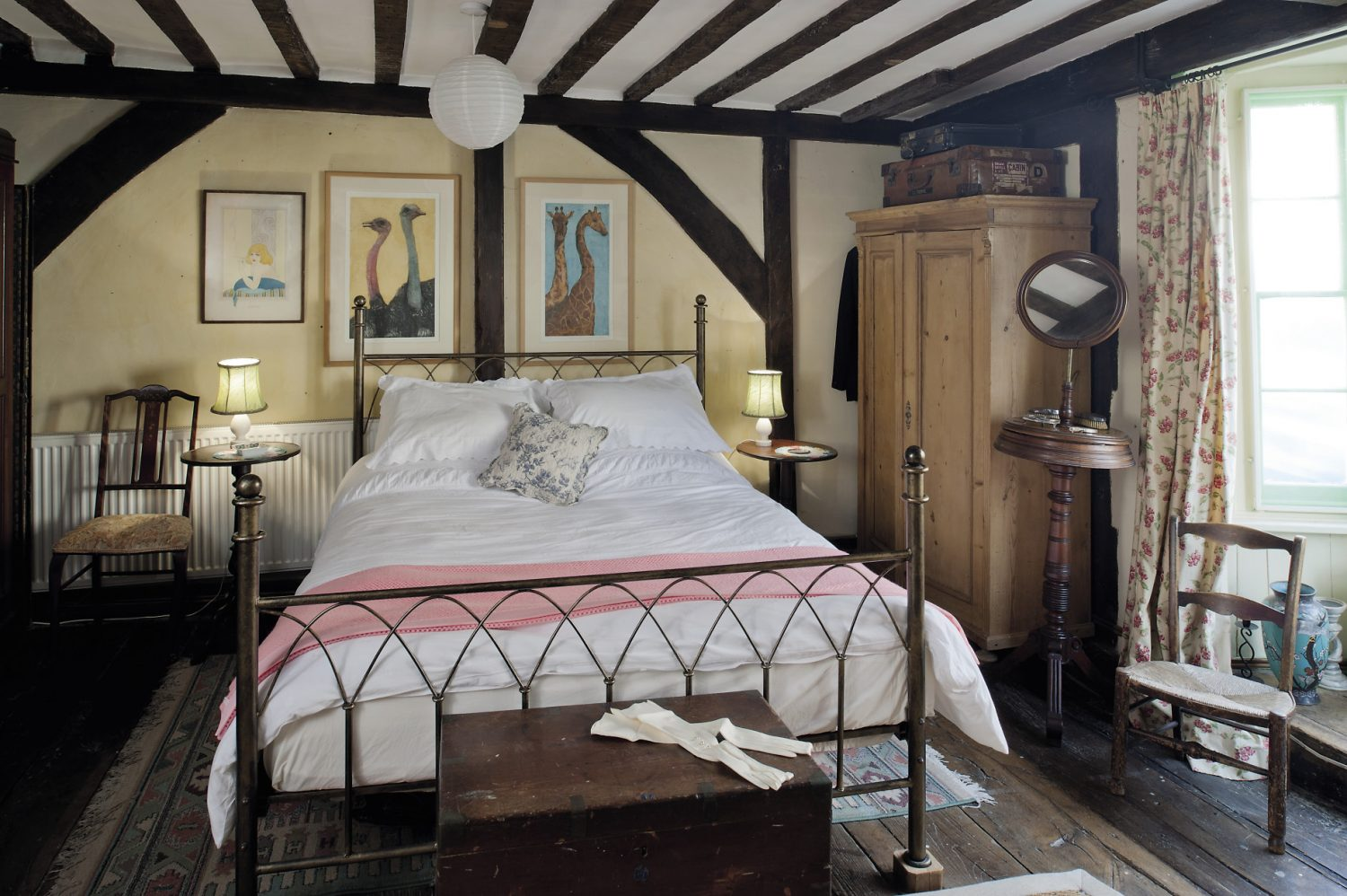 On the wall above the gothic style iron bed in the guest bedroom there are two paintings of an ostrich and giraffe by artist Tor Hilyard