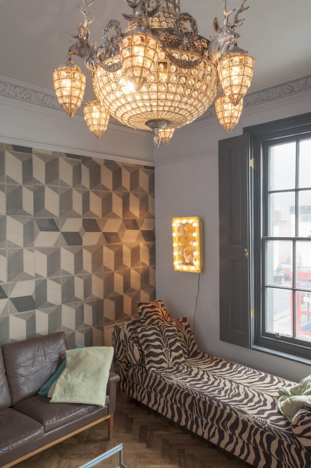 Geometric grey wallpaper lines the rear wall of the cosy 'snug' sitting room, whilst a zebra-print chaise longue is positioned next to the shuttered window