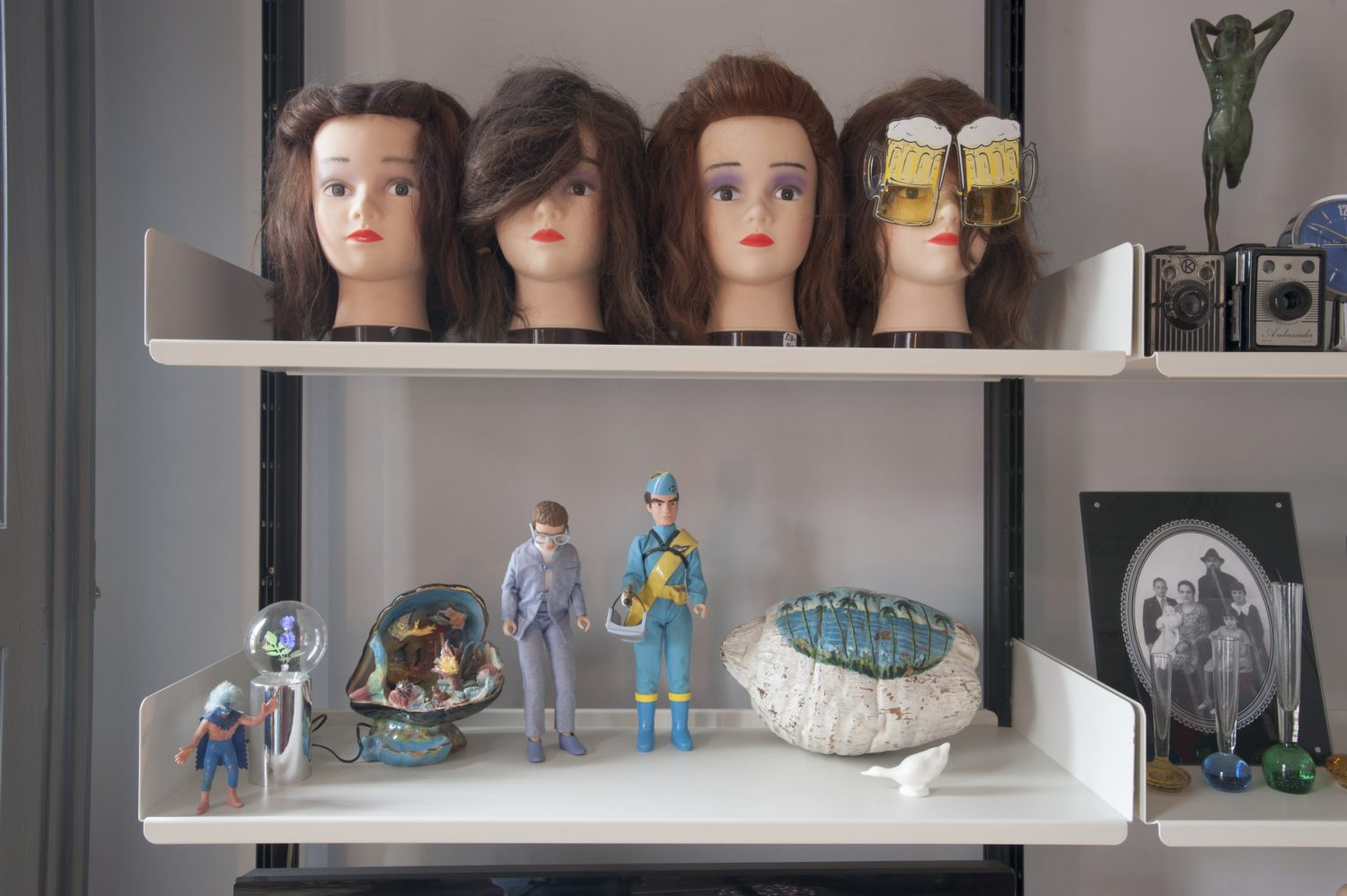 Hairdressing training heads line one shelf in the sitting room