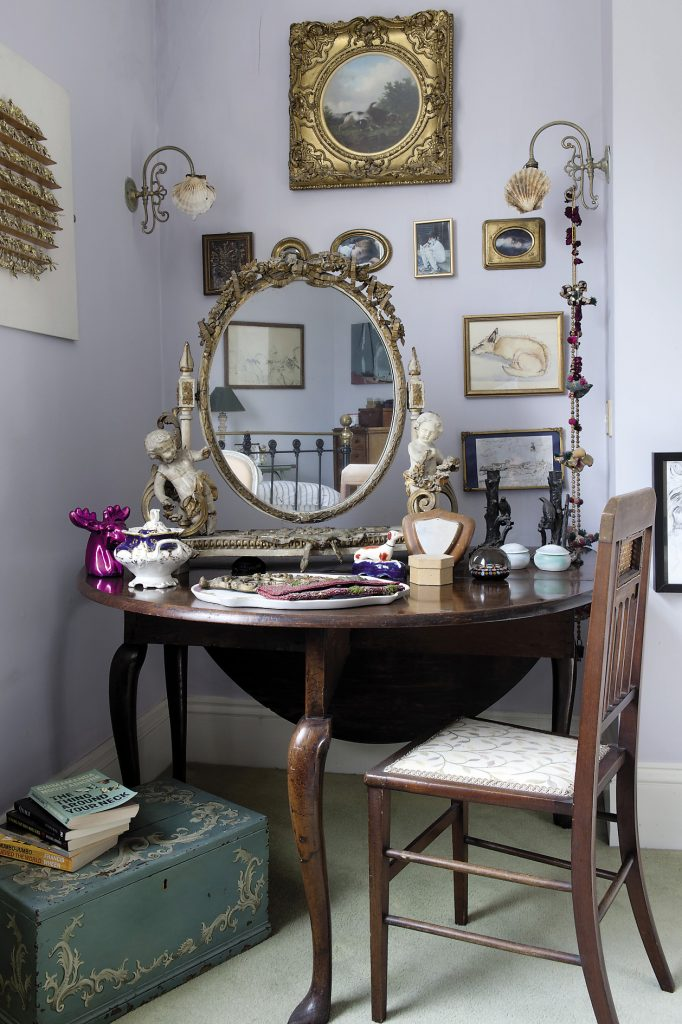 In the far corner of the master bedroom a circular wooden table supports a fantastically ornate dressing mirror that is decorated with swags of carved ribbons and roses and flanked by a pair of cherubs