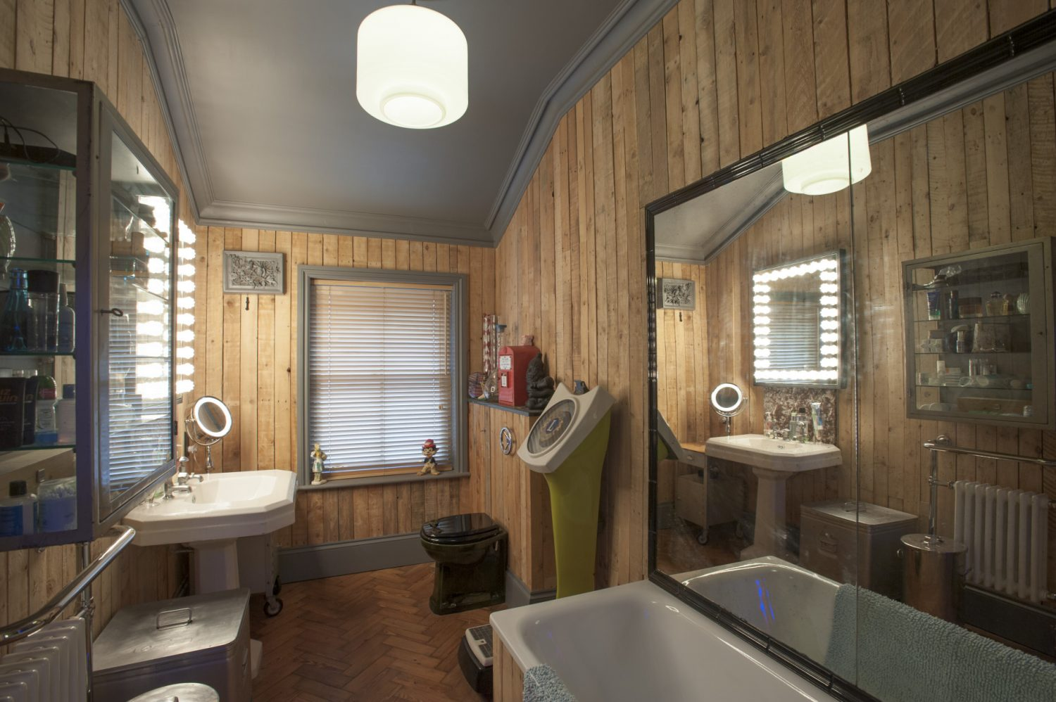 The timber-clad bathroom is home to an old full length, glass-fronted-and-sided surgical cabinet and French basin – another Old Town find. Old penny-in-the-slot scales stand beside the loo, the flush handle for which is a chrome wheel valve-opener from a fire engine