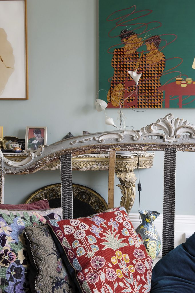 An extravagantly styled Rococo console table with a marbled paper top stands against the wall opposite the fireplace but above it and to the side there are bold, contemporary paintings