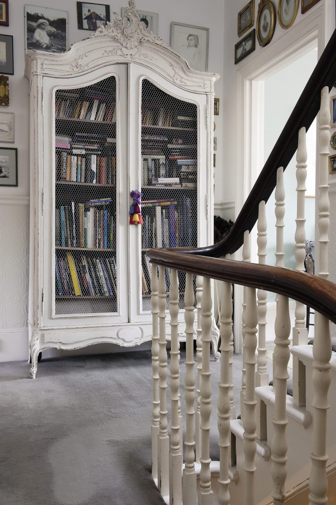 On the first floor landing a large painted French armoire, packed with books, has had its original panels replaced with chicken wire