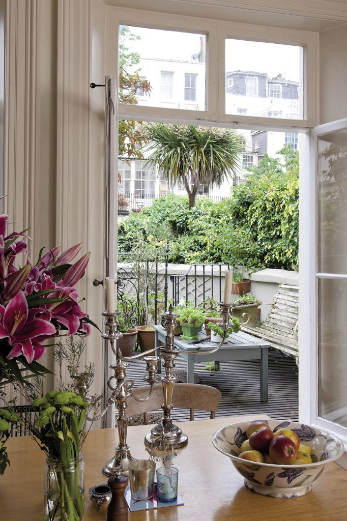 Huge French windows open out from the kitchen onto a decked verandah and overlook a paved lower terrace that is stylishly planted with old-fashioned roses, lavender and neatly trimmed box and bay