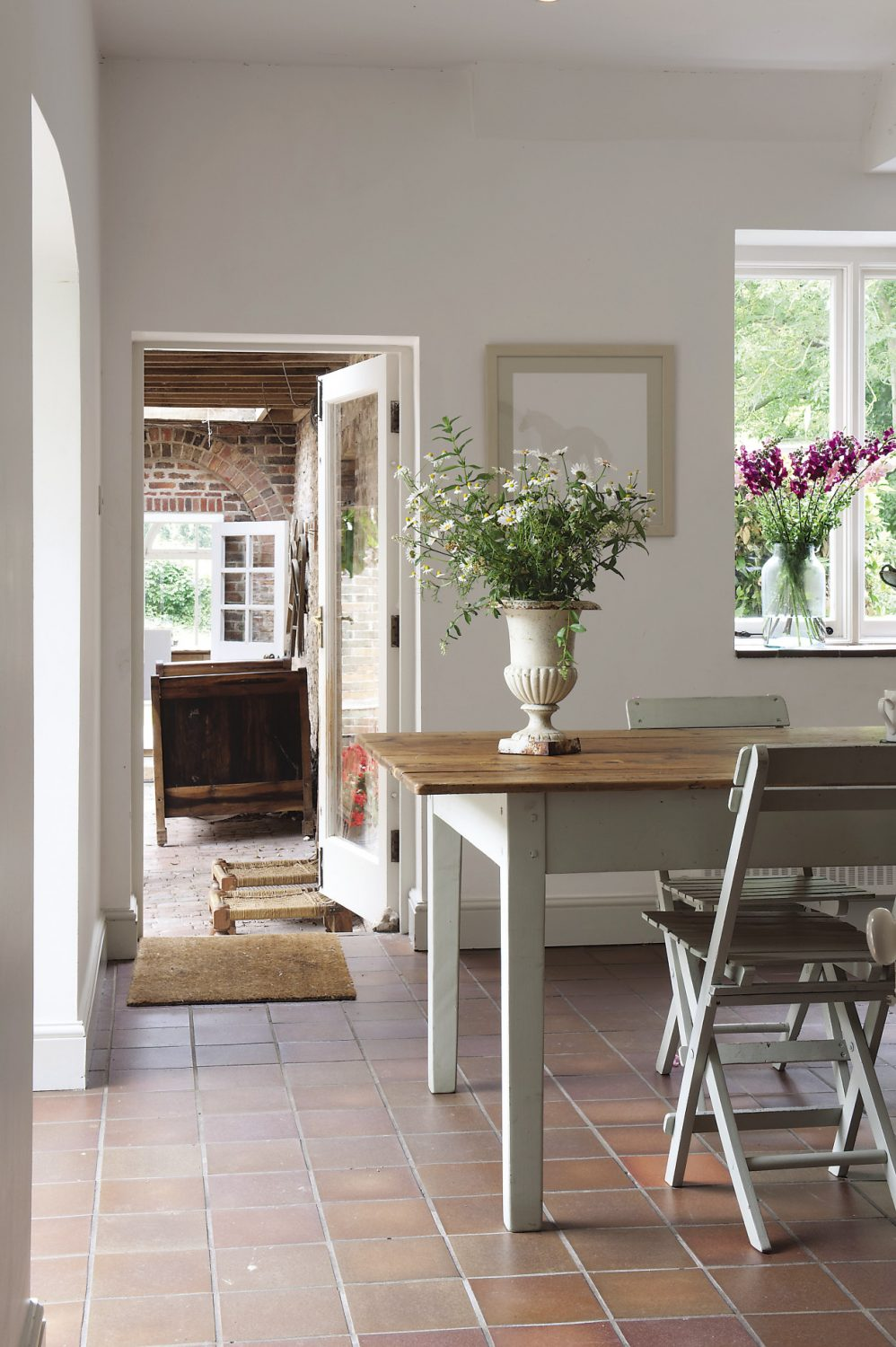 On the upper level of the kitchen there is a long wooden table, one of a pair made by a local carpenter in Polegate