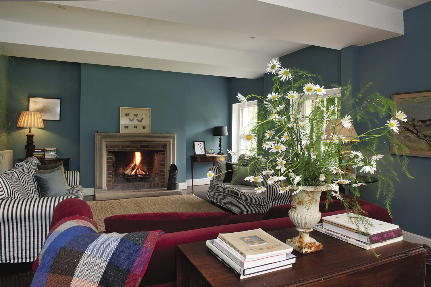 Across the wide hallway is the drawing room. A pair of striped sofas face each other in front of the fireplace and a garnet red velvet sofa has its back to the window overlooking the courtyard