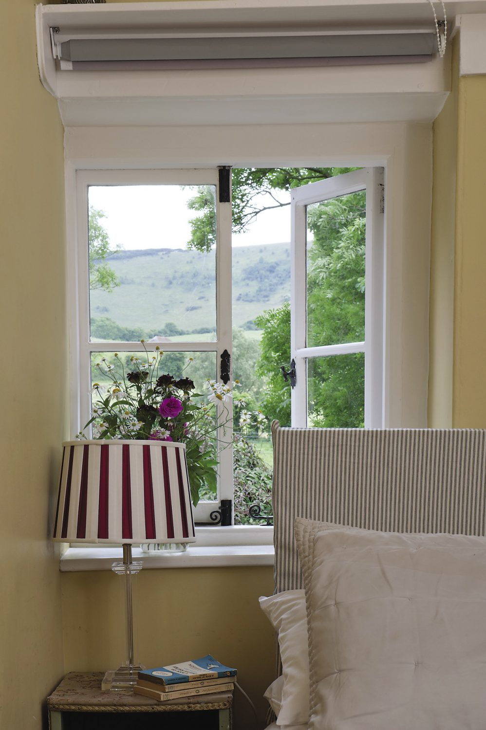 The guest bedrooms and bathrooms are decorated in varying shades of olive and moss green and are all simply furnished with grey silk curtains, mahogany or painted chests of drawers and adorned with simple posies of flowers cut from the garden