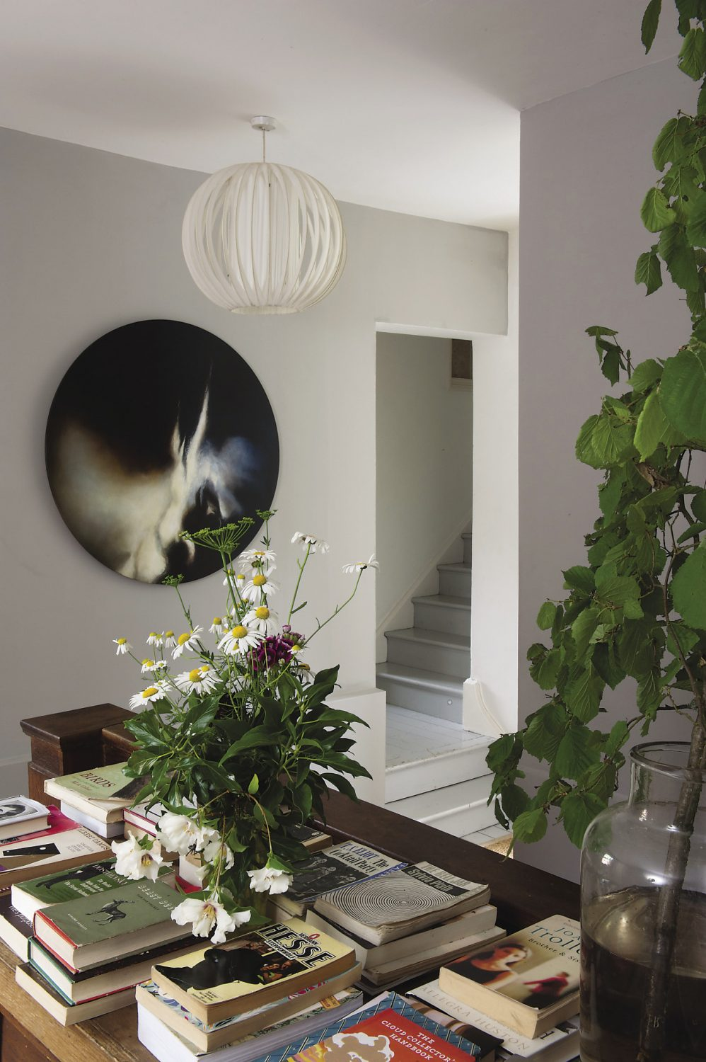 """Upstairs, the landing features another """"tree in a jar"""", its crisp green leaves make a wonderful contrast to the pale grey walls. """"We used the same grey paint colour up here as in the library. I mixed most of the colours in the house myself,"""" says Polly"""