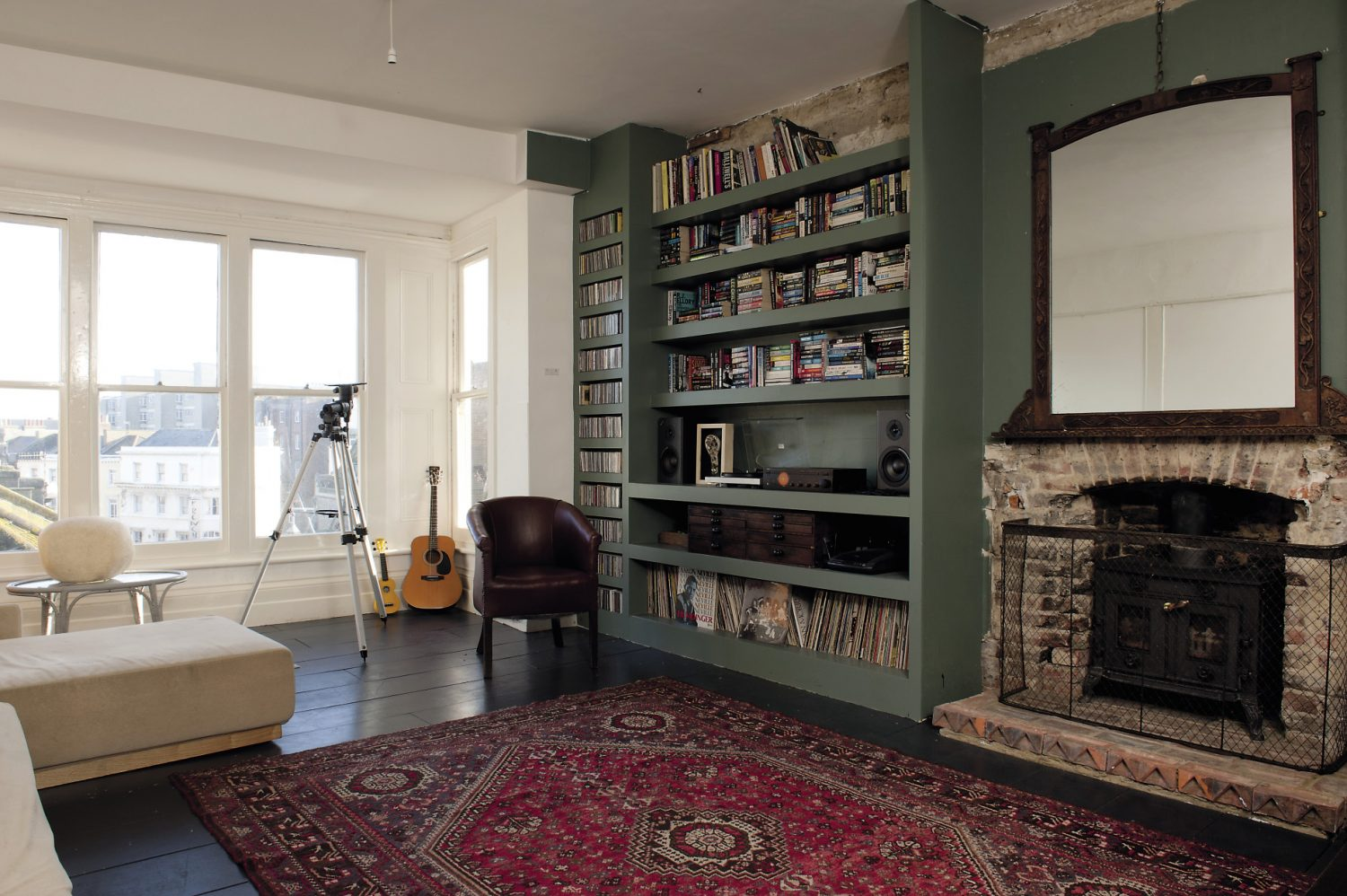 The library gathers around an original brick fireplace, above which hangs an arts and crafts mirror. The windows look out over another wonderful roofscape and towards the sea. A tangle of staircases connects the apartment and B&B with the rest of the building...