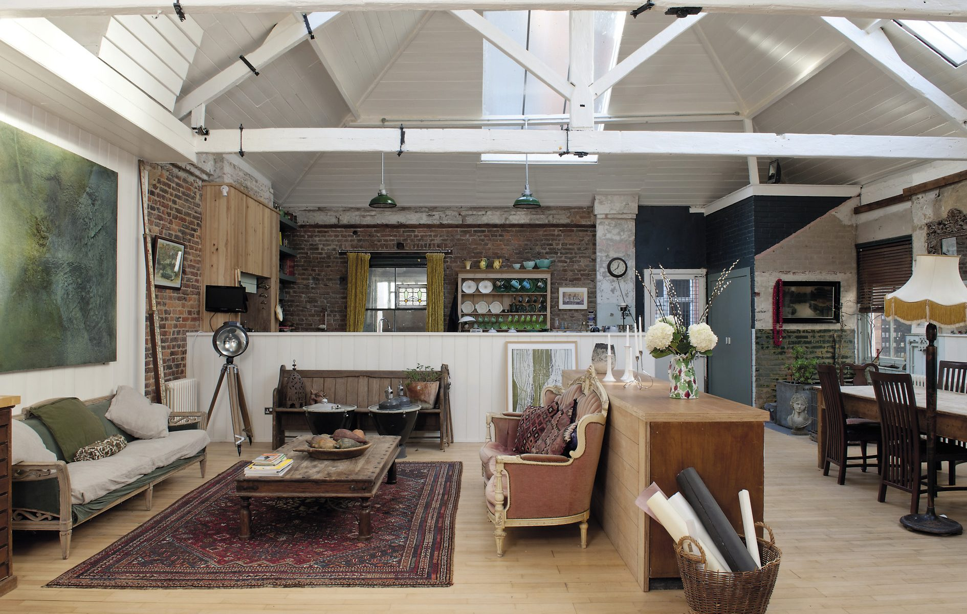 The living room, that also incorporates the kitchen and a dining area, is truly vast, soaring up past huge white-painted beams to the pitched roof. On one side the walls are of bare brick and on the other of age-damaged render