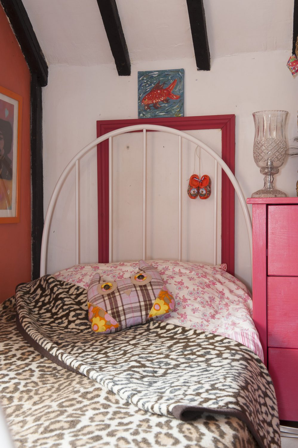 The shared bedroom features leopard-skin bed covers, a great shocking pink and blue chests of drawers, pink and white standard lamp and a wonderful dining chair that Oeda has painted pink and upholstered in a pale green and pink rose fabric