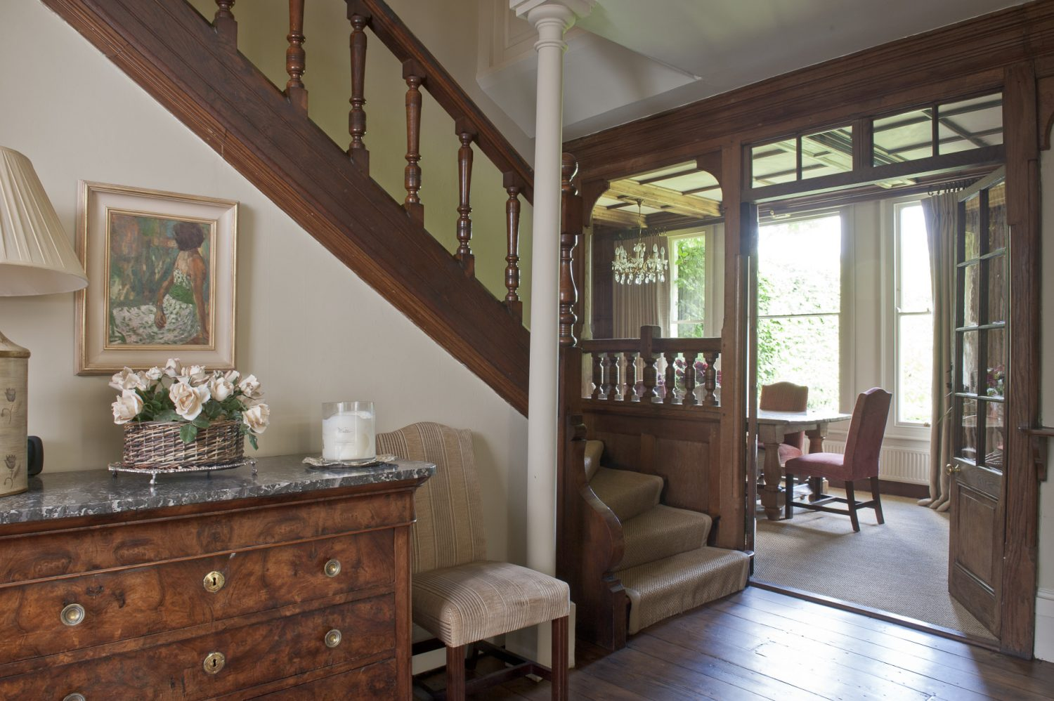 The stately windows allow light to flood into this room illuminating the wood-panelled walls