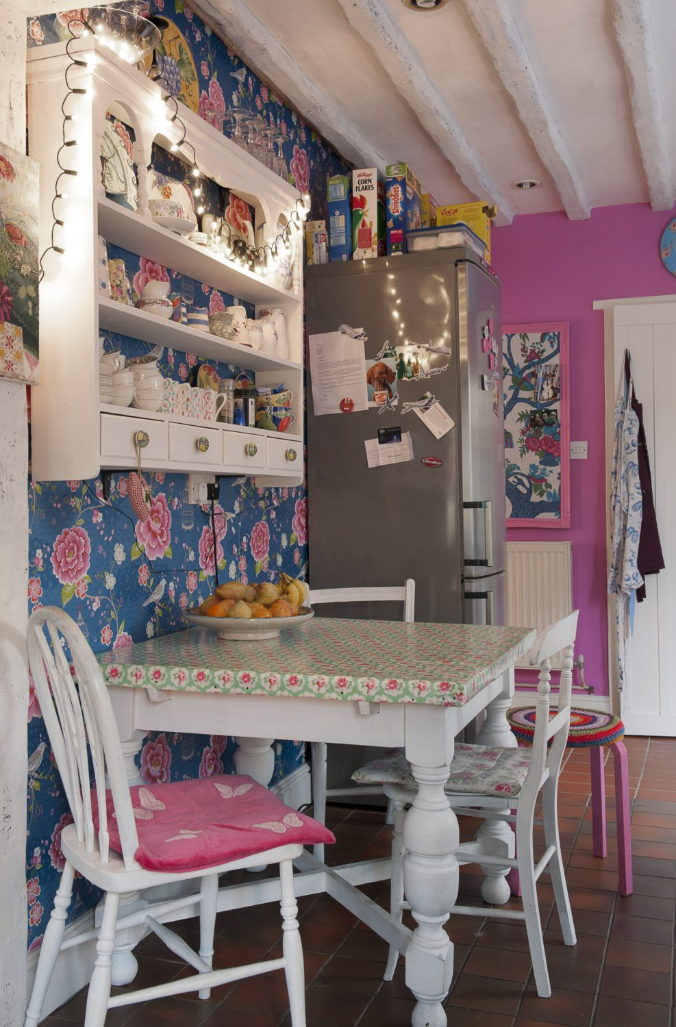 One wall of the vibrant pink kitchen is papered with 'Birds in Paradise' by Pip Studio
