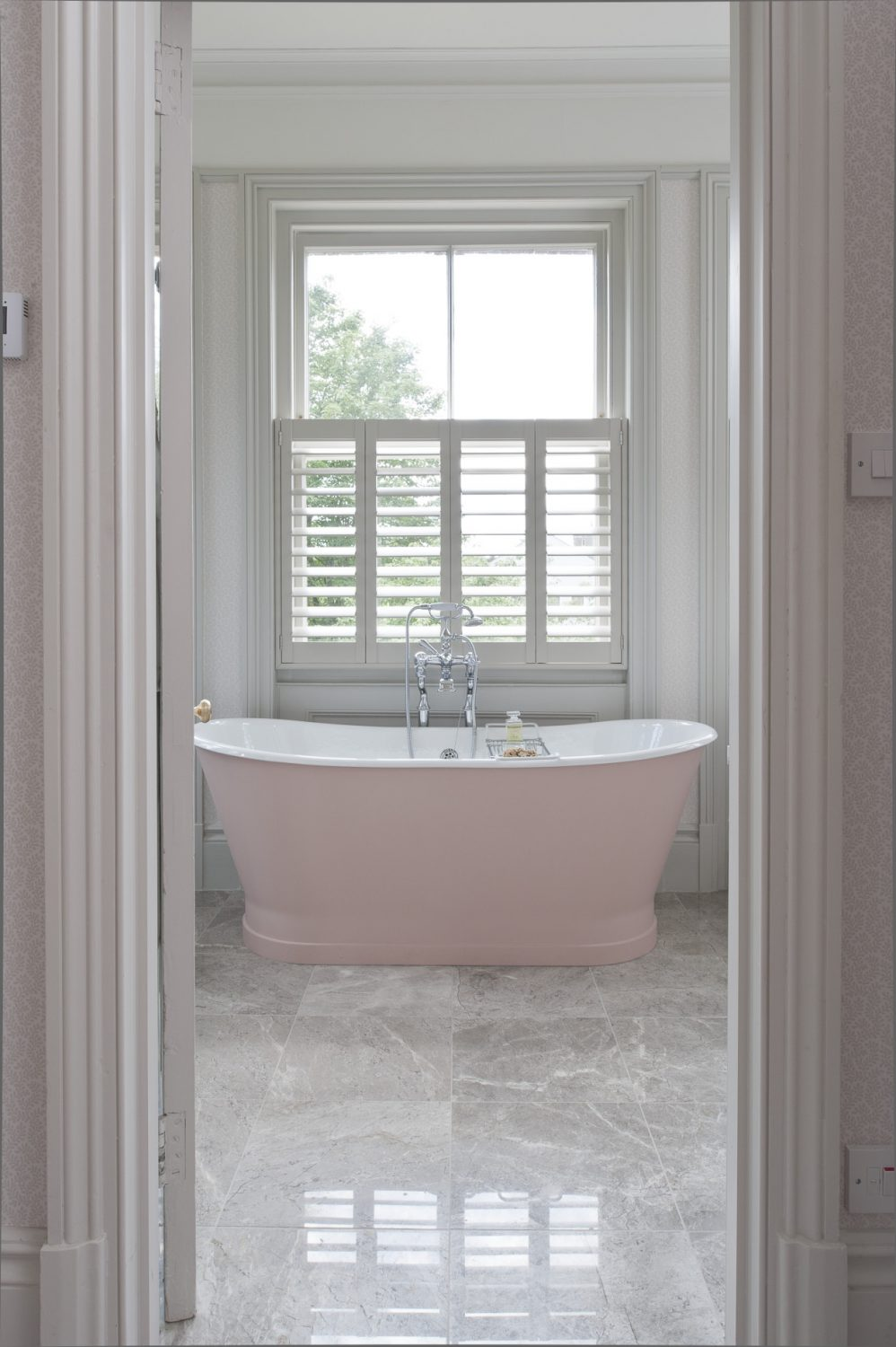 The shell pink bath sits in the centre of the marble-floored master bathroom; shutters provide privacy without losing light
