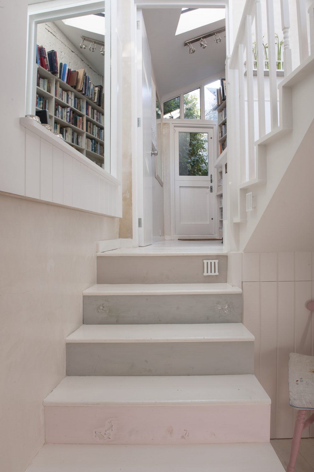 A white staircase, into which Karl has carved the occasional tiny fairy, flower, frog, leads down from Jessica's office into the girls' den