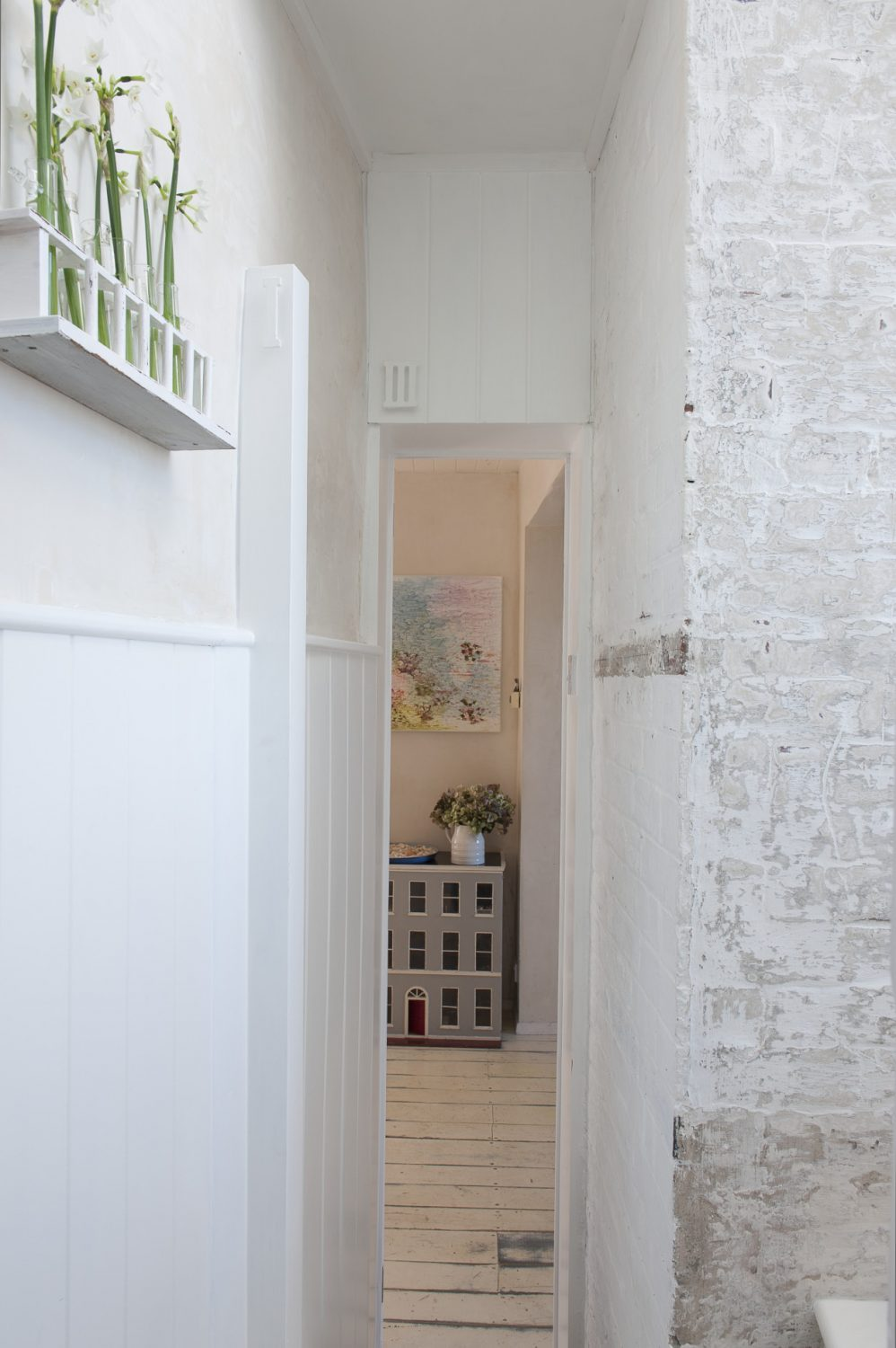 The bright white walls illuminate even the most modest of spaces. On a wall is a former test-tube rack, painted white, the tubes filled with water and delicate single stems of tiny white flowers