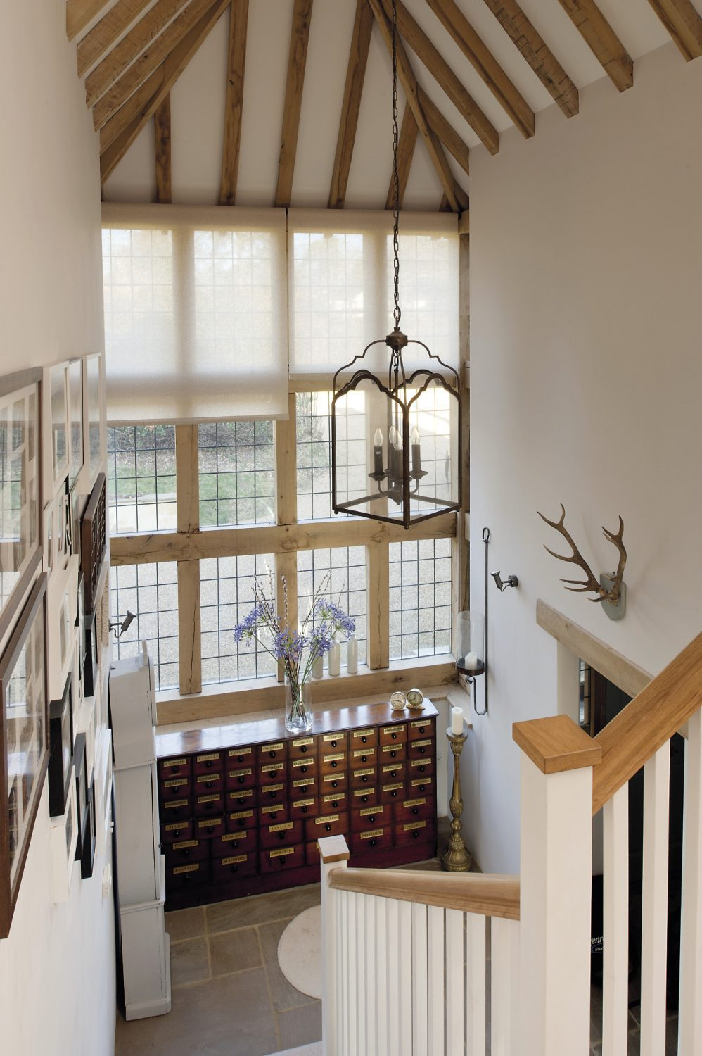 As you enter the house, light floods in from the superb two-storey oak-framed window. A pitched, oak-beamed ceiling soars above the staircase, from which hangs a magnificent lantern. Beneath the window is a huge mahogany former pharmacy cabinet
