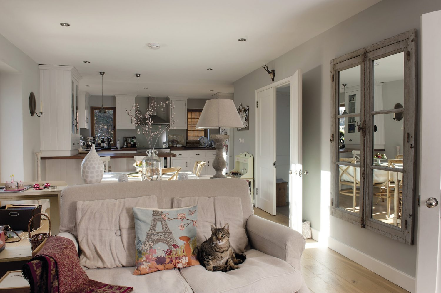 A lovely window from a French chateau has been fitted with mirrored glass and mounted on the wall opposite the room's true window