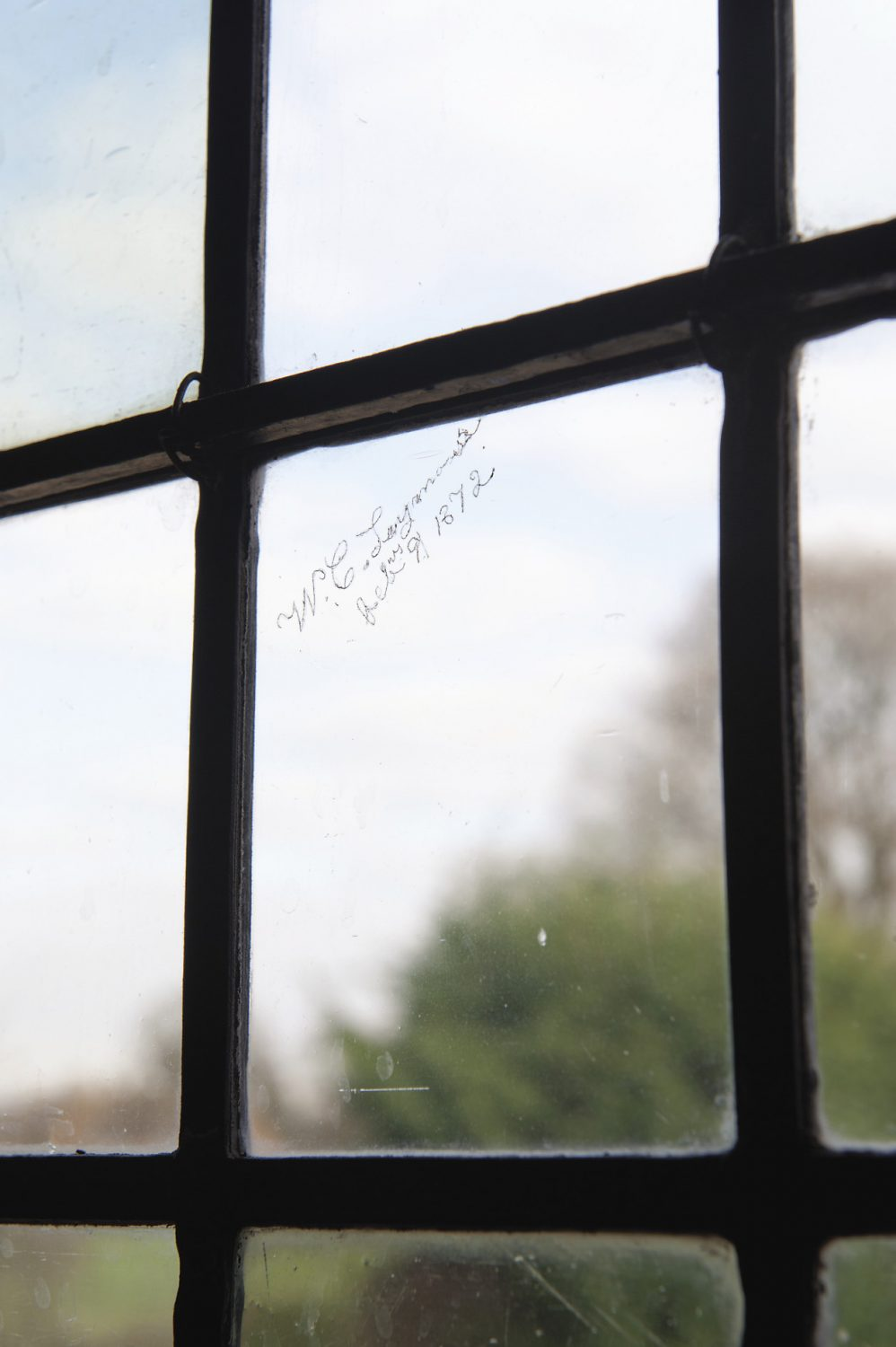A leaded-light window that has developed such a slope over the centuries that it looks as if it is somehow melting away at one end. In one tiny pane of glass there is a signature in neat copperplate script: W.C. Laymouth, February 9th 1872. And high up at the top, David and Daphne have recently spotted another signature, but this time it has been etched on the glass from the outside...