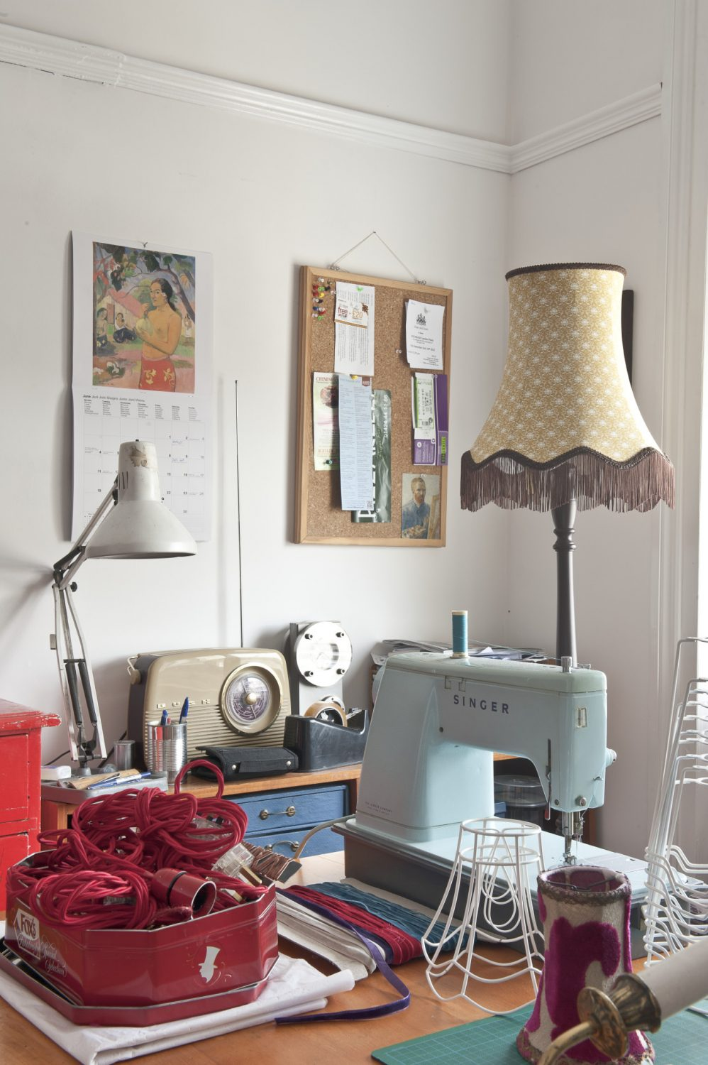Charlotte's 'den' where she designs and makes her lampshades. A simple table stands in front of the window and on top of it is a smart but rather old-fashioned-looking sky blue Singer sewing machine