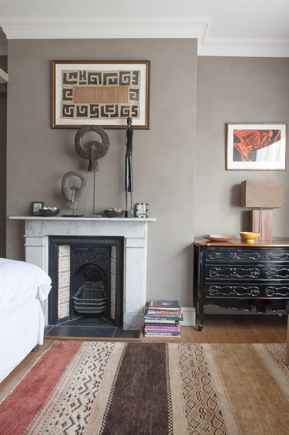In the Saadi bedroom African buffalo masks and a tribal figure stand tall above the fireplace. The colours are earthier, but very contemporary and the fresh white bedlinen and pale marble fireplace make a crisp contrast