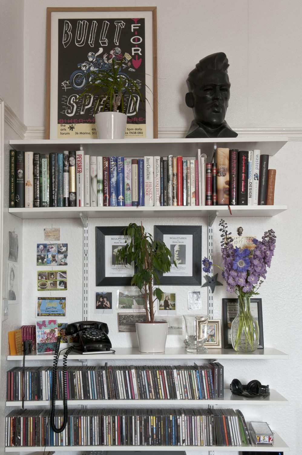 In one corner, several sets of shelves are crammed with books and pictures, including the poster for a recent exhibition in Hastings called Built for Speed and a black resin bust of Elvis by local artist, Mark Selby