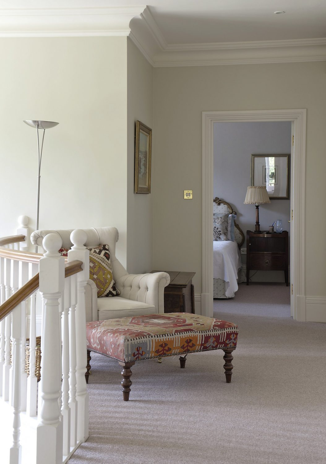 Across the landing, the guest bedroom features a gilded three-armed chandelier with forget-me-not blue silk shades covering the candle bulbs. A huge painted armoire from Portugal has three large blue and white jars from northern Portugal on the top