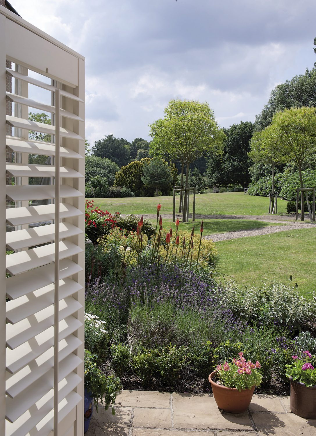 """Ro's garden wraps around the building's southern wall, too, and is planted with lavender, roses, ceanothus and alchemilla mollis. """"I've just come back from Hampton Court Show, so I'm full of ideas."""""""