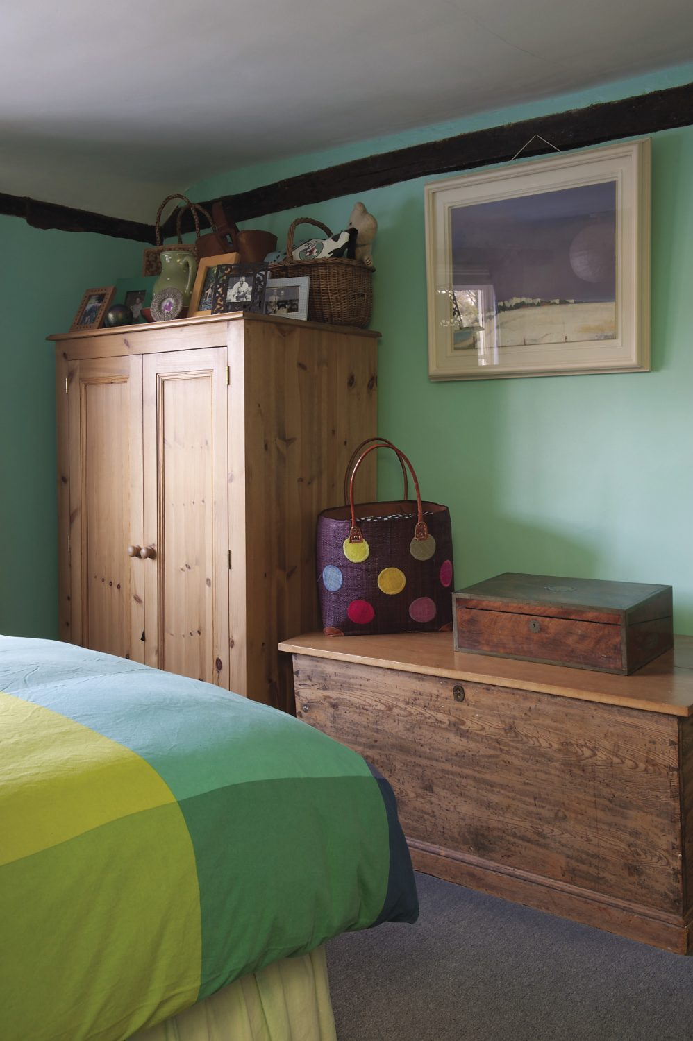 """In the master bedroom, on a scrubbed pine chest, stands a raffia shopping basket with brightly coloured spots like giant Smarties arranged over it. """"I bought that for Fiona,"""" says Oliver. """"It's never actually been used for shopping, but the colours are just irresistible."""""""