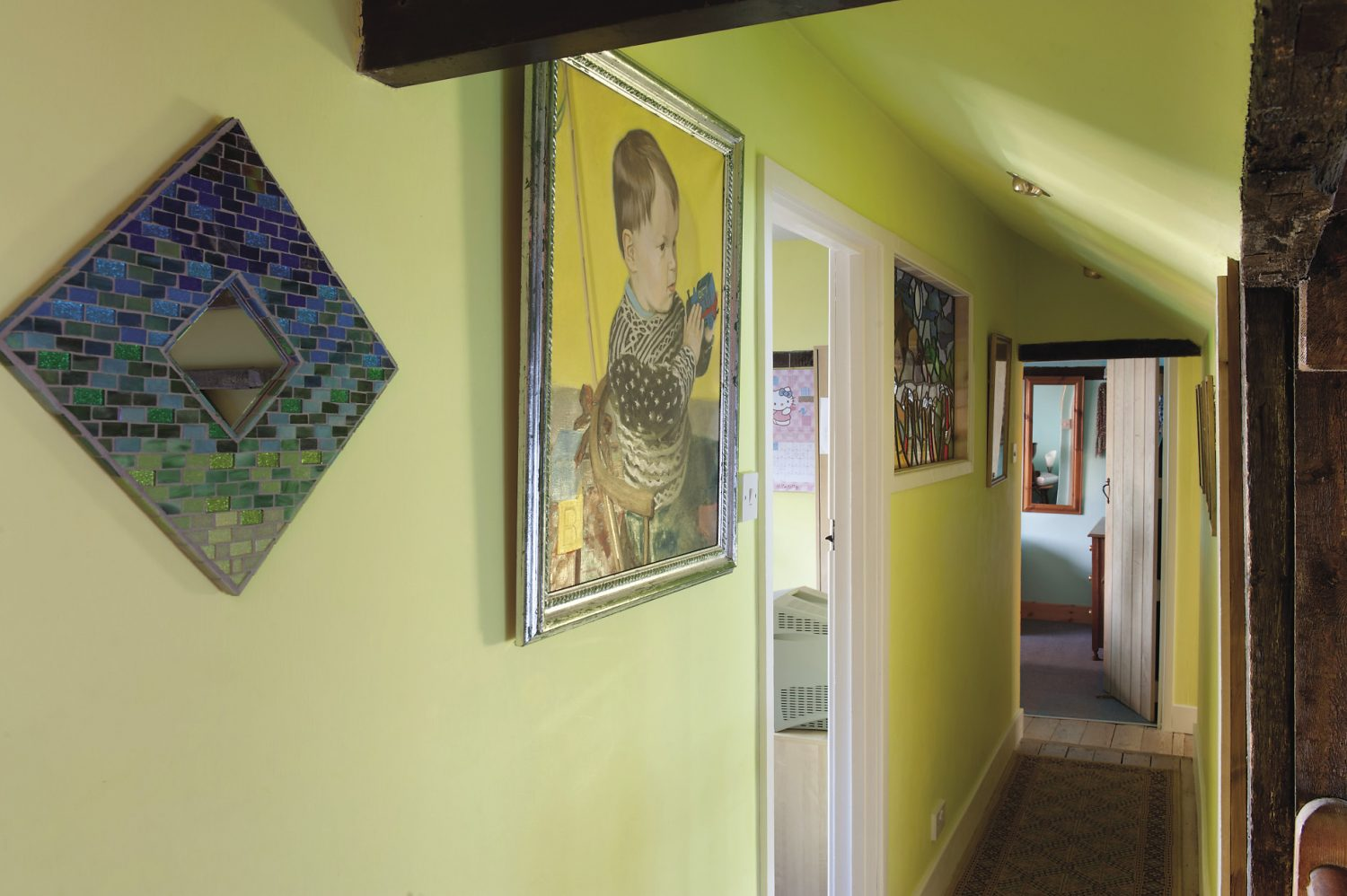 On the wall at the top of the wooden staircase, there is a striking painting of the couple's son, by Stephen Rose