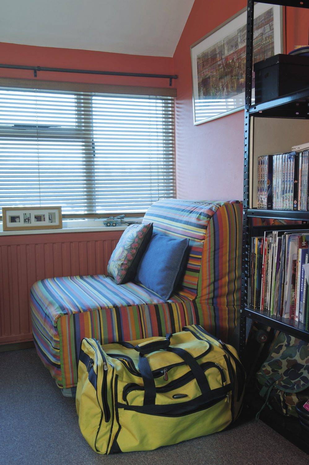 The couple's son's room already shows all the telltale signs of the architectural student. Every item of furniture is placed at right angles to the watermelon red walls (architects never seem to place anything on the diagonal) and there is a striped chair in front of the window where curtains have been rejected in favour of simple wooden Venetian blinds