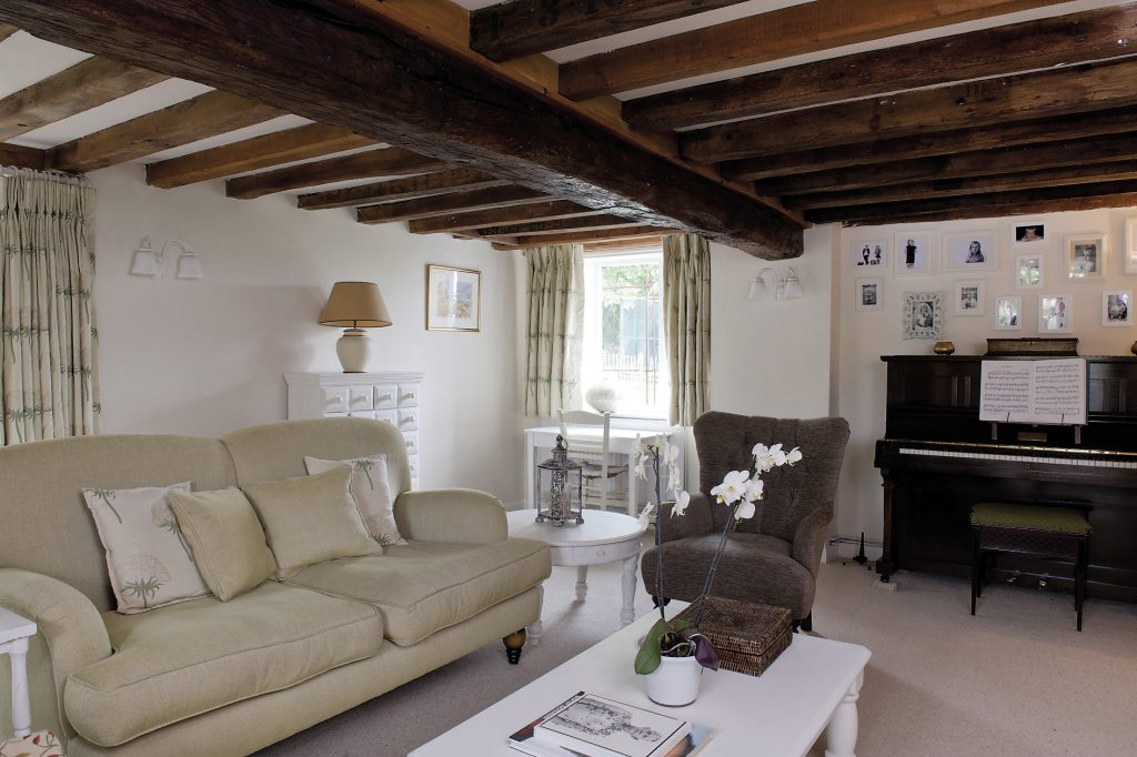 In the sitting room, the original beams remain as do the previous owner's curtains. Against one wall is the couple's son's piano and against another a heavy 28-draw chest that came with the family back from Dubai