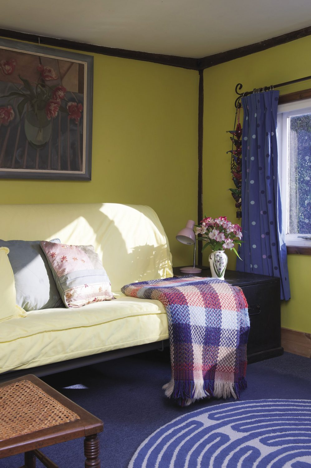 Light pours in through the window in the spare room, bringing its bright yellow walls to life
