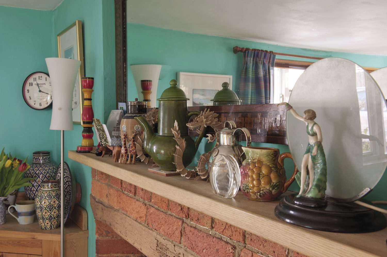 A long mirror with an inlaid wooden frame hangs above the fireplace. The mantelpiece is home to an Arts & Crafts Doulton jug, an olive green lidded pot brought back from a trip to France, a collection of painted wooden African animals and a pair of vibrant candlesticks