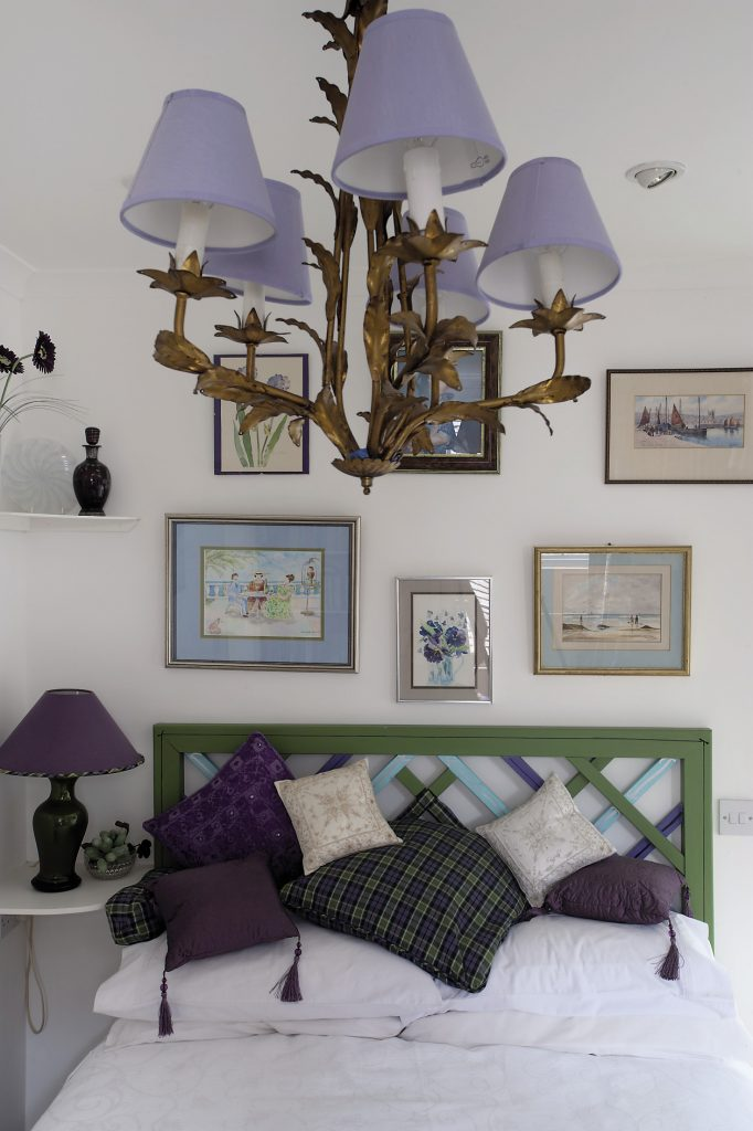 Carpenter Ken Gates, who also made the bedroom door bookcases, made the guestroom's bedhead, which hangs on the wall rather than being attached to the divan. It has been painted emerald and navy to match the valance and floor-length pure silk curtains