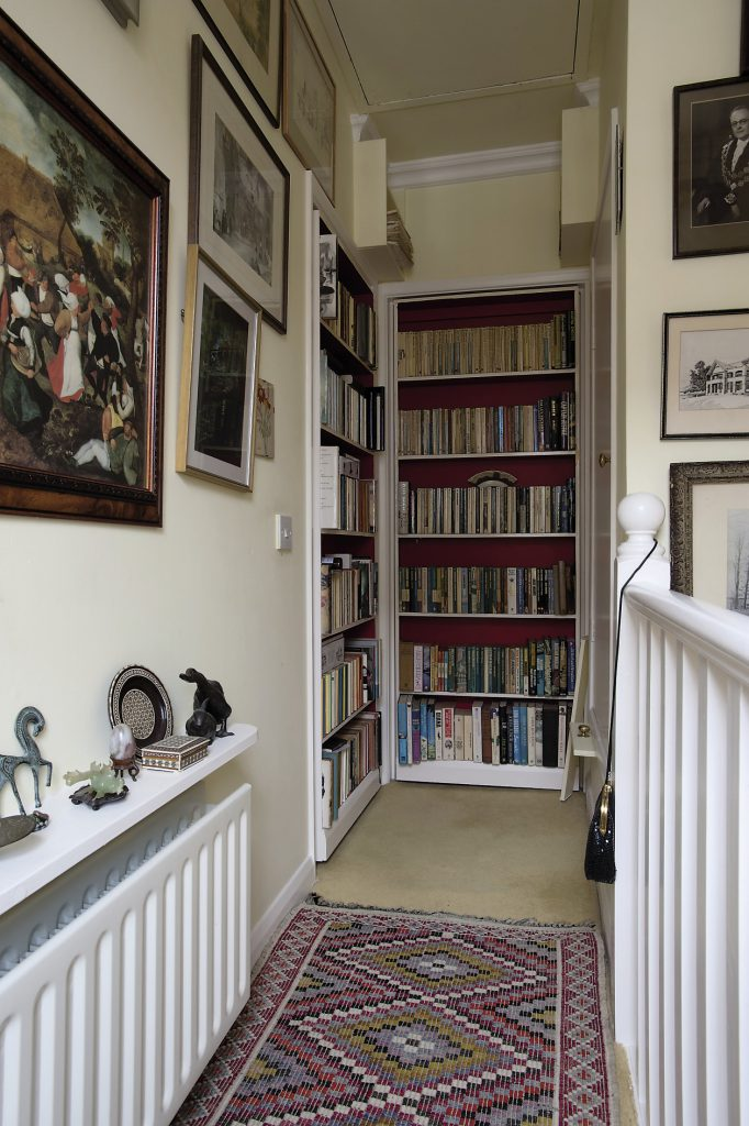 Two seemingly fixed bookcases at the end of the landing swing back to reveal the master bedroom and guestroom. The walls on the ascent to the first floor are filled with cherished family photographs and artworks